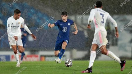 Chelsea's Christian Pulisic runs with the ball between Real Madrid's Raphael Varane, left, and Eder Militao, right, during the Champions League semifinal first leg soccer match between Real Madrid and Chelsea at the Alfredo di Stefano stadium in Madrid, Spain