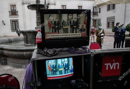 Chile's President Sebastian Pinera is televised on screens from a news crew during a press conference at La Moneda government palace in Santiago, Chile, . Pinera suffered a new defeat regarding the withdrawal of private pension funds after the Constitutional Court rejected his request to declare unconstitutional an already approved bill that allows millions of Chileans to withdraw up to 10% of their retirement savings
