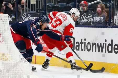 Detroit Red Wings' Sam Gagner, right, tries to control the puck as Columbus Blue Jackets' Michael Del Zotto defends during the first period of an NHL hockey game, in Columbus, Ohio