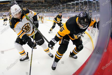 Pittsburgh Penguins' Mike Matheson (5) and Boston Bruins' Patrice Bergeron (37) work for procession of the puck in the corner during the second period of an NHL hockey game in Pittsburgh
