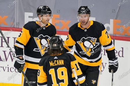 Pittsburgh Penguins' Jeff Carter (77) celebrates with Mike Matheson (5) and Jared McCann (19) after scoring during the third period of an NHL hockey game in Pittsburgh