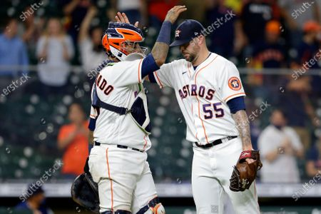 Stock Picture of Houston Astros catcher Martin Maldonado (15) and closing pitcher Ryan Pressly (55) pat each other on the head after the Astros' 2-0 win over the Seattle Mariners in a baseball game, in Houston