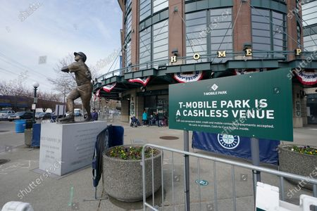 Stock Image of Sign noting that T-Mobile Park is a cashless ballpark is displayed next to the statue of Seattle Mariners' Ken Griffey Jr. on opening day before a baseball game between the Mariners and the San Francisco Giants, in Seattle