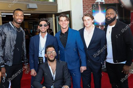 Miles Boykin, left, wide receiver for the Baltimore Ravens, poses with actor RJ Mitte, center, Otaro Alaka, right, linebacker for the Baltimore Ravens, and others at the film premiere for 'Triumph'