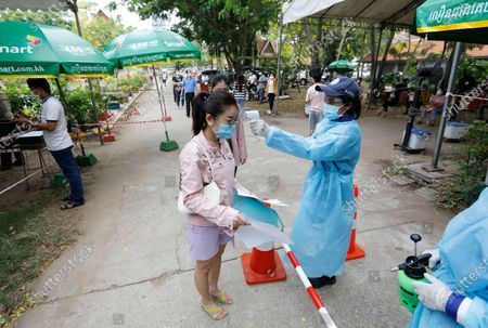 A woman has her temperature checked during a vaccination drive held at a center in Phnom Penh, Cambodia, 28 April 2021. On 27 April 2021 Cambodian Prime Minister Hun Sen ordered a national COVID-19 vaccination campaign for all people aged 18 and over, starting with the lockdown areas 'Red Zone' in Phnom Penh after a spike in COVID-19 cases in the country.