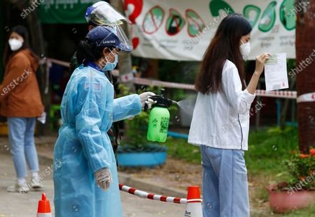 A health worker sprays disinfectant on a woman to prevent the spread of COVID-19 during a vaccination drive held at a center in Phnom Penh, Cambodia, 28 April 2021. Cambodian Prime Minister Hun Sen on 27 April 2021 ordered a national COVID-19 vaccination campaign for all people aged 18 and over, starting with the lockdown areas 'Red Zone' in Phnom Penh after a spike in Covid-19 cases in the country.