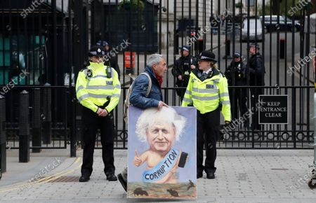 """Painter Kaya Mar walks past the entrance gate to 10 Downing Street in London, . British Prime Minister Boris Johnson has denied a press report which quoted him as allegedly saying he would rather see """"bodies pile high in their thousands"""" than impose a third national lockdown on the country. The Daily Mail claimed that Johnson made the comment in the fall of 2020, when his government imposed a second lockdown to combat a surge in coronavirus cases"""