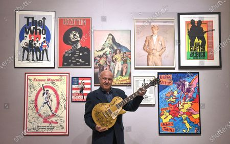 Harvey Goldsmith poses with the multi-signed Les Paul gold Top guitar signed at Bob Dylan's ÔThe 30th Anniversary concert', estimated £10,000 -£15,00 and some of his collection of signed posters, and music-world mementoes at Bonhams in the Knightsbridge.