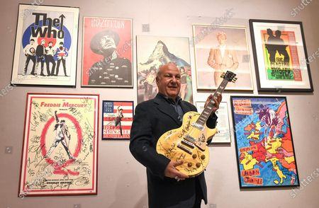Harvey Goldsmith poses with the multi-signed Les Paul gold Top guitar signed at Bob Dylan's 'The 30th Anniversary concert', estimated £10,000 -£15,00 and some of his collection of signed posters, and music-world mementoes at Bonhams in the Knightsbridge.