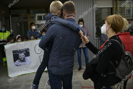 Woman touches the hand of a young relative of Spanish reporter David Beriain, during a minute's silence in the small town where Beriain was born, in Artajona, northern Spain, . Beriain was one of two Spanish journalists and the Irish director of a wildlife foundation that were killed Monday in an ambush in eastern Burkina Faso. The two journalists were working with the wildlife campaigner on a documentary about poachers in a national park bordering Benin when they were attacked by gunmen