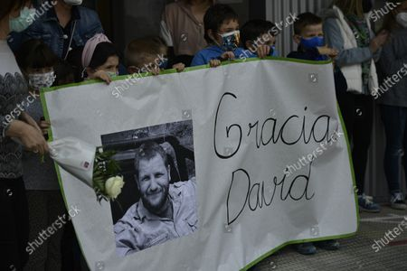 """Young students hold a banner with a portrait of Spanish reporter David Beriain reading, """"Thanks David"""", during a minute's silence in the small town where Beriain was born, in Artajona, northern Spain, . Beriain was one of two Spanish journalists and the Irish director of a wildlife foundation that were killed Monday in an ambush in eastern Burkina Faso. The two journalists were working with the wildlife campaigner on a documentary about poachers in a national park bordering Benin when they were attacked by gunmen"""