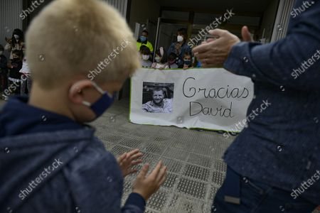 Young relative of Spanish journalist David Beriain applauds while young students hold a portrait of him, during a minute's silence in the small town where Beriain was born, in Artajona, northern Spain, . Beriain was one of two Spanish journalists and the Irish director of a wildlife foundation that were killed Monday in an ambush in eastern Burkina Faso. The two journalists were working with the wildlife campaigner on a documentary about poachers in a national park bordering Benin when they were attacked by gunmen