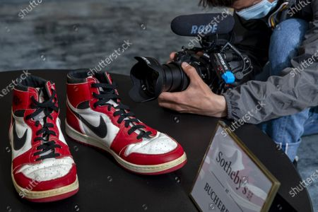 A reporter films shoes of former NBA player Michael Jordan Game Worn 1985 Player Sample Air Jordan 1s estimated to sell between 100,000 and 150,000 Swiss francs (CHF), during a Sotheby's preview at the boutique Buchere, in Geneva, Switzerland, 28 April 2021. Sotheby's presents 'Gamers Only', a selective online auction of game-worn sneakers from some of basketball's greatest athletes until 12 May.