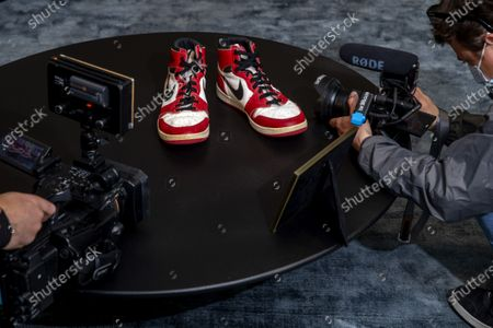 Reporters films shoes of former NBA player Michael Jordan Game Worn 1985 Player Sample Air Jordan 1s estimated to sell between 100,000 and 150,000 Swiss francs (CHF), during a Sotheby's preview at the boutique Buchere, in Geneva, Switzerland, 28 April 2021. Sotheby's presents 'Gamers Only', a selective online auction of game-worn sneakers from some of basketball's greatest athletes until 12 May.