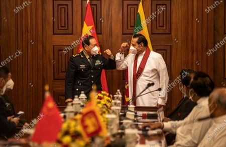 Sri Lankan Prime Minster Mahinda Rajapaksa, right, and Chinese Defence Minister Wei Fenghe fist bump as they avoid traditional hand shake as a precaution against the coronavirus during their meeting in Colombo, Sri Lanka