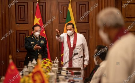 Sri Lankan Prime Minster Mahinda Rajapaksa, right, and Chinese Defence Minister Wei Fenghe wearing masks as a precaution against the coronavirus gesture during their meeting in Colombo, Sri Lanka