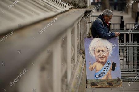 """Political artist Kaya Mar holds one of his paintings of British Prime Minister Boris Johnson near the entrance to Downing Street, before Johnson was driven past to go to the Houses of Parliament in London, for the weekly Prime Minister's Questions, . Britain's Electoral Commission, which regulates political finance in the U.K, is launching a formal investigation of the refurbishment of Prime Minister Boris Johnson's apartment on Downing Street, saying there were """"reasonable grounds"""" to suspect an offense had been committed"""