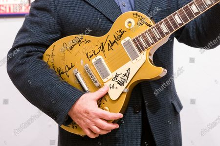 English performing arts promoter, Harvey Goldsmith poses with the multi-signed Les Paul gold top guitar signed at Bob Dylan's 30th Anniversary Concert and some of his collection of signed poster and music momentos at Bonhams Art Gallery in London, Britain, 28 April 2021. A collection of guitars, signed posters, and music-world mementoes belonging to world-renowned music promoter and producer Harvey Goldsmith will be offered for sale at auction by Bonhams on 05 May 2021.