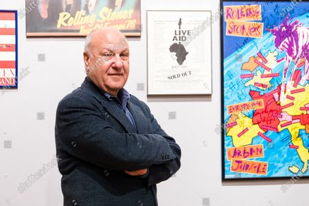 English performing arts promoter, Harvey Goldsmith poses with some of his collection of signed poster and music momentos at Bonhams Art Gallery in London, Britain, 28 April 2021. A collection of guitars, signed posters, and music-world mementoes belonging to world-renowned music promoter and producer Harvey Goldsmith will be offered for sale at auction by Bonhams on 05 May 2021.