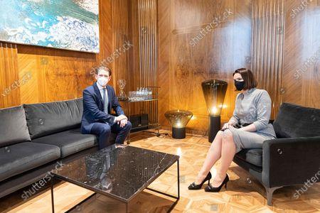 Austrian Chancellor Sebastian Kurz, left, talks to Belarusian opposition leader Sviatlana Tsikhanouskaya, wearing a protective face mask, at the federal chancellery in Vienna, Austria