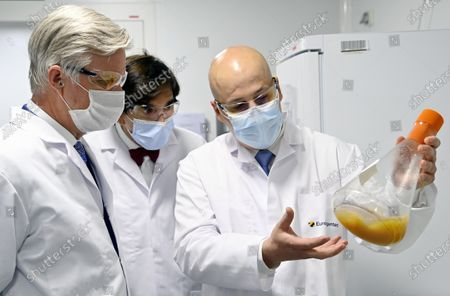 Stock Image of King Philippe of Belgium (L) and Wallonia Minister President Elio Di Rupo (C) look on during a visit to Eurogentec, a company working on the development of therapies against the COVID-19 Coronavirus, in Seraing, Bekgium, 28 April 2021. The King exchanged with the management on the importance of Eurogentec's activities in Belgium on the prospects for Belgian biotechnology companies and the challenges that come with it. He also paid a visit to the laboratory where the DNA and RNA molecules are developed as well as the restricted area where they are produced.