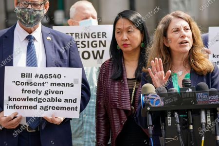 Jean Kim, second from right, listens as her attorney Patricia Pastor, right, speaks to reporters during a news conference, in New York. Kim, who once worked as an unpaid intern for City Comptroller Scott Stringer, a contender to become New York City's next mayor, accused him Wednesday of groping her without consent. Stringer denied the allegations