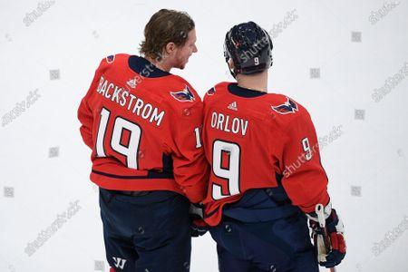 Washington Capitals center Nicklas Backstrom (19) and defenseman Dmitry Orlov (9) warm up before an NHL hockey game against the New York Islanders, in Washington