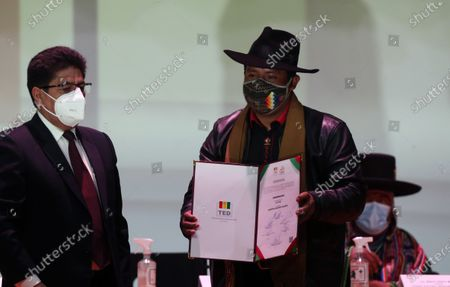 Santos Quispe (R), of the Jallala group, receives from the President of the Departmental Electoral Tribunal (TED) of La Paz, Franz Jimenez (L), the credential as Governor-elect of La Paz, Bolivia, 28 April 2021. The TED of La Paz delivered the credentials to the authorities who were elected in the subnational elections so that they can exercise their functions from next 03 May.