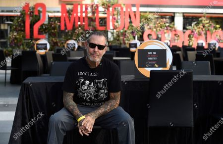 Mike Ness of the rock band Social Distortion sits at one of the 48 empty tables set up at the ONE VOICE event, in honor of the live events industry which has been devastated by the COVID-19 pandemic, at L.A. Live in Los Angeles
