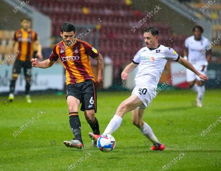 Stock Photo of Bradford City's Anthony O'Connor plays the ball back to goal despite the attention of Salford City's Ian Henderson  during the Sky Bet League 2 match between Bradford City and Salford City at the Utilita Energy Stadium, Bradford, England on 27th April 2021.