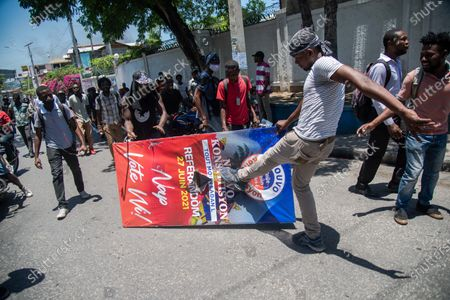 Haitian students kick a promotional banner of the draft Constitution promoted by President Jovenel Moise, during a protest against this projected Magna Carta and against the wave of violence and kidnappings that is shaking the country, in Port-au-Prince, Haiti, 28 April 2021. President Moise intends to submit his projected new Constitution to a popular vote at the end of June, but the opposition refuses to participate in the process.