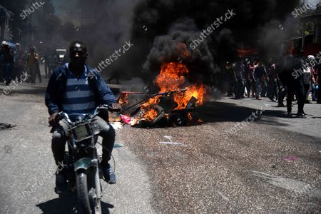 Haitian citizens pass next to promotional banners of the draft Constitution promoted by President Jovenel Moise set on fire by students, during a protest against this projected Magna Carta and against the wave of violence and kidnappings that is shaking the country, in Port-au-Prince, Haiti, 28 April 2021. President Moise intends to submit his projected new Constitution to a popular vote at the end of June, but the opposition refuses to participate in the process.