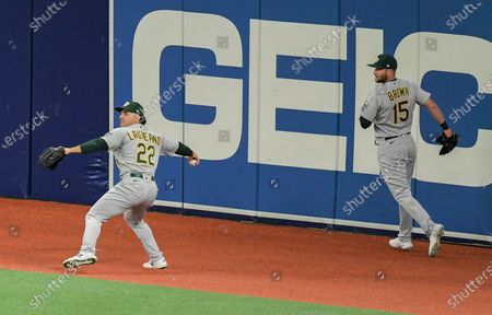 Oakland Athletics' Seth Brown (15) backs up Ramon Laureano (22), who throws the ball after fielding a double off the wall hit by Tampa Bay Rays' Manuel Margot during the first inning of a baseball game, in St. Petersburg, Fla
