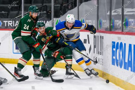 Minnesota Wild defenseman Matt Dumba (24) and center Nico Sturm, center, and St. Louis Blues center Ryan O'Reilly try to control the puck during the second period of an NHL hockey game, in St. Paul, Minn. The Blues won 4-3
