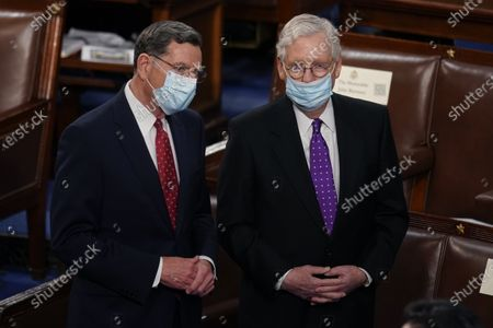 Sen. John Barrasso, R-Wyo., and Senate Minority Leader Mitch McConnell of Ky., stand after President Joe Biden spoke to a joint session of Congress, in the House Chamber at the U.S. Capitol in Washington