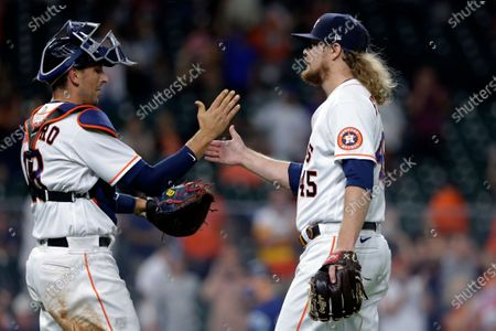 Houston Astros catcher Jason Castro (18) and closing pitcher Ryne Stanek (45) celebrate the Astros' 7-5 win over the Seattle Mariners in a baseball game, in Houston