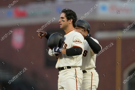 San Francisco Giants' Michael Tauchman, left, talks with first base coach Antoan Richardson against the Colorado Rockies during a baseball game in San Francisco