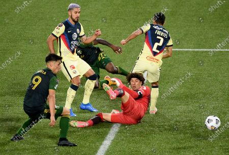 América goalkeeper Guillermo Ochoa, right, close in on Portland Timbers forward Felipe Mora, left, during the second half of a CONCACAF Champions League soccer match in Portland, Ore., . The match ended in a 1-1 draw