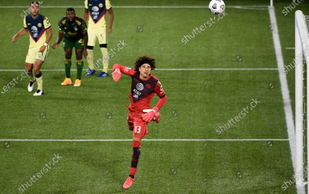 América goalkeeper Guillermo Ochoa watches as a shot by Portland Timbers forward Dairon Asprilla, second from left, sails over the goal during the second half of a CONCACAF Champions League soccer match in Portland, Ore., . The match ended in a 1-1 draw