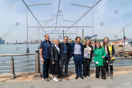 Stock Photo of Laurie Tisch (2nd from left), museum director Adam Weinberg (center), Co-director of Estate of Gordon Matta-Clark Jane Crawford (3rd from right) among guest attend The Whitney Museum of American Art of David Hammons sculpture Day's End installation on Gansevoort Peninsula. Sculpture resembles original Pier 52 shed in slender steel beams measuring 52 feet high at its peak and installed on the same location where shed was. Sculpture draws its inspiration and name from a 1975 Gordon Matta-Clark project. Day's End embodies the Museum's mission in supporting living artists to realize their visions, serving the community, and connecting to the public through art.