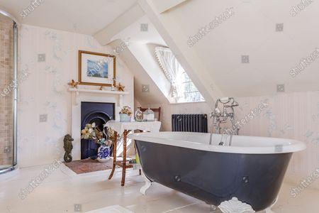 Stock Photo of Bathroom.   A grand Georgian manor where writer Evelyn Waugh lived and died is on the market for £5.5m.  The author of Vile Bodies, Brideshead Revisited and Sword of Honour bought Combe Florey House in Somerset in 1956 and his family lived there until 2008 when they sold it to the current owners.  In Waugh's day the house was often filled with his glamorous and clever guests like poet John Betjeman, actors Peter Cook and Alec Guinness and writers Salman Rushdie and Muriel Spark.  The 12-bedroom house has had a makeover since Waugh's day and quirky style and is now a light-filled spacious family home with a party barn, swimming pool and 34 acres.