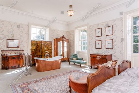 Bedroom with bath.   A grand Georgian manor where writer Evelyn Waugh lived and died is on the market for £5.5m.  The author of Vile Bodies, Brideshead Revisited and Sword of Honour bought Combe Florey House in Somerset in 1956 and his family lived there until 2008 when they sold it to the current owners.  In Waugh's day the house was often filled with his glamorous and clever guests like poet John Betjeman, actors Peter Cook and Alec Guinness and writers Salman Rushdie and Muriel Spark.  The 12-bedroom house has had a makeover since Waugh's day and quirky style and is now a light-filled spacious family home with a party barn, swimming pool and 34 acres.