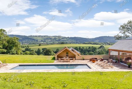 Stock Image of Outdoor pool.   A grand Georgian manor where writer Evelyn Waugh lived and died is on the market for £5.5m.  The author of Vile Bodies, Brideshead Revisited and Sword of Honour bought Combe Florey House in Somerset in 1956 and his family lived there until 2008 when they sold it to the current owners.  In Waugh's day the house was often filled with his glamorous and clever guests like poet John Betjeman, actors Peter Cook and Alec Guinness and writers Salman Rushdie and Muriel Spark.  The 12-bedroom house has had a makeover since Waugh's day and quirky style and is now a light-filled spacious family home with a party barn, swimming pool and 34 acres.