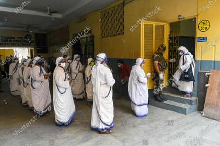 Sisters of Missionaries of Charity wait in queue in front of a polling station to cast their vote during the final phase of West Bengal assembly elections in Kolkata , India , on 29 April 2021 .
