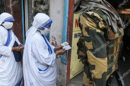 A sister of Missionaries of Charity shows her Voter ID card to a CRPF personal before she is allowed inside a polling station in Kolkata , India , on 29 April 2021 .