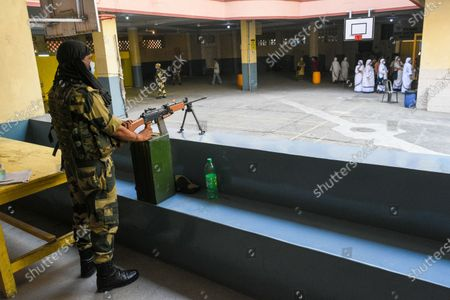 A CRPF personal stands guard at a polling station in Kolkata , India , on 29 April 2021 .