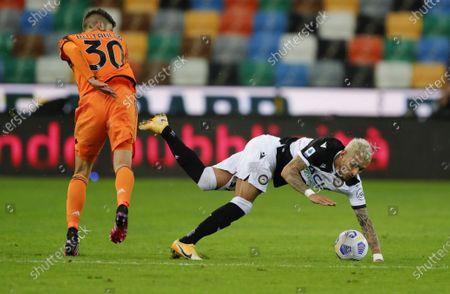 Udinese's Roberto Pereyra goes to ground after clashing with Rodrigo Bentancur.