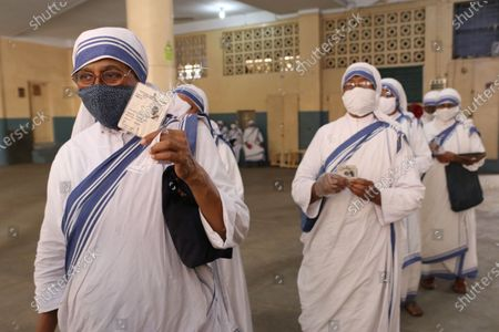 Missionary of Charity Nuns wearing mask shows their voter id card as they queued in front of a polling station, during 8th phase of West Bengal assembly elections in Kolkata, India on 29 April, 2021. The 8th phase of West Bengal Assembly Election 2021 ahead COVID-19 CORONAVIRUS pandemic situation.