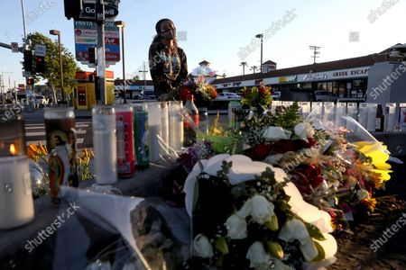 Stock Image of Liliana Ruiz, of Los Angeles, stops at a memorial to pay her respect for Alexis Carbajal, 24, who was shot and killed by Carlos Lopez, 49, who went on a shooting rampage, at the Starbucks near 28th Street and Figueroa, on Wednesday, April 28, 2021 in Los Angeles, CA. Carlos Lopez, 49, went on a shooting rampage in Los Angeles - killing two people and wounding two others - he was fatally shot by police after a standoff on the 91 Freeway in Fullerton. (Gary Coronado / Los Angeles Times)