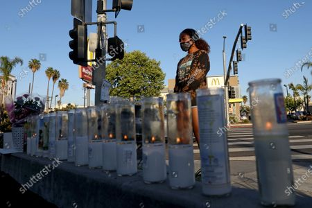 Stock Picture of Liliana Ruiz, of Los Angeles, stops at a memorial to pay her respect for Alexis Carbajal, 24, who was shot and killed by Carlos Lopez, 49, who went on a shooting rampage, at the Starbucks near 28th Street and Figueroa, on Wednesday, April 28, 2021 in Los Angeles, CA. Carlos Lopez, 49, went on a shooting rampage in Los Angeles - killing two people and wounding two others - he was fatally shot by police after a standoff on the 91 Freeway in Fullerton. (Gary Coronado / Los Angeles Times)